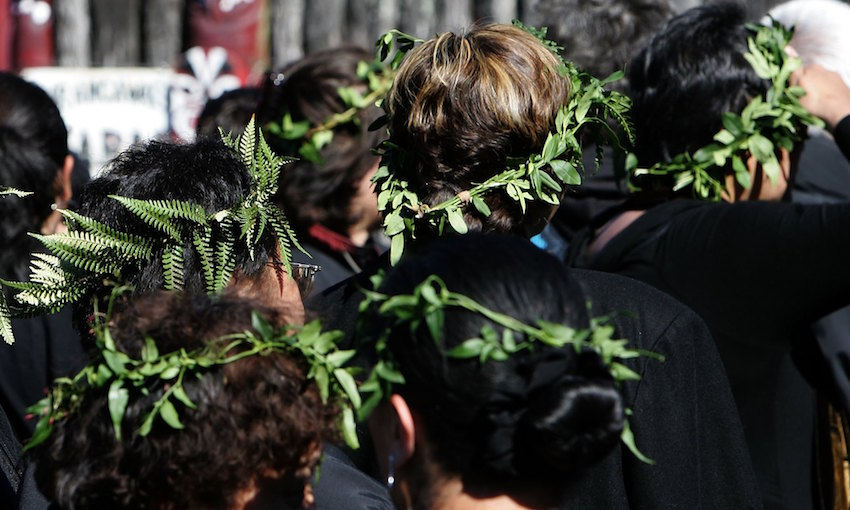 A group of Māori women wearing pare kawakawa, wreaths of kawakawa leaves on their heads as a sign of mourning.