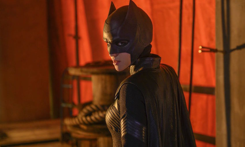 Batwoman, without a wig, looks mysteriously over her shoulder in a red-lit room