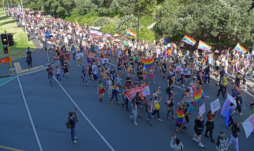 Three thousand marchers block Auckland central roads waving pride flags.