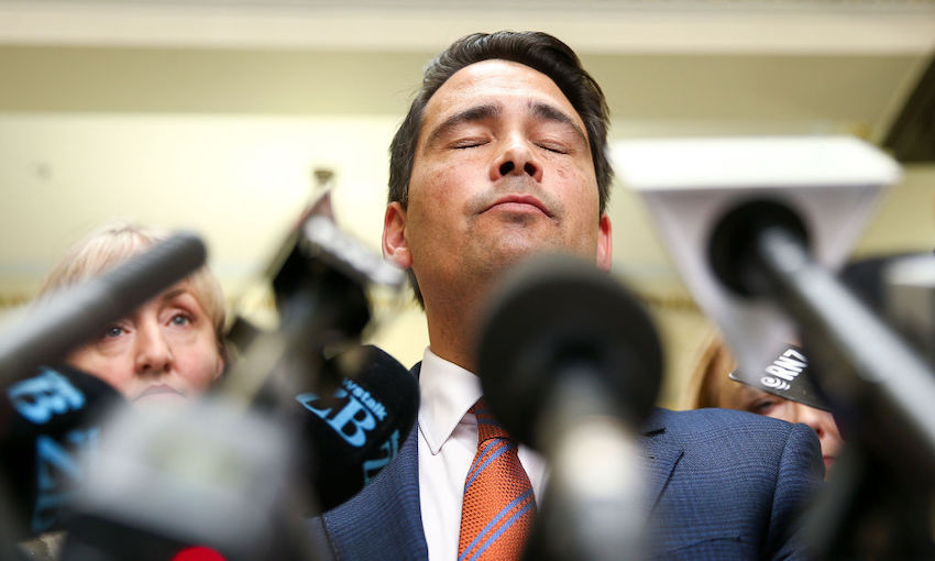 Photo of a middle-aged politician, eyes closed, chin raised, during a press conference bristling with microphones