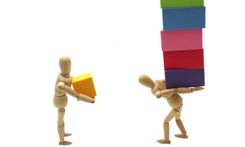 one figure holding small box, the other holding a stack of boxes. Unfair burden concept