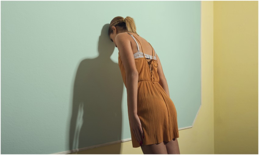 rear view of woman leaning head against wall