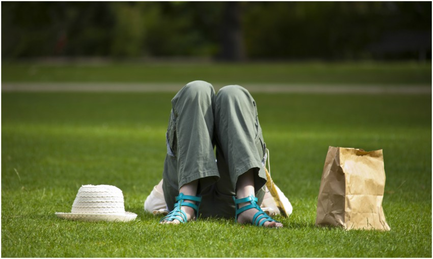 Person lying on their back on grass, we see their bent knees, a hat and paper bag beside them.