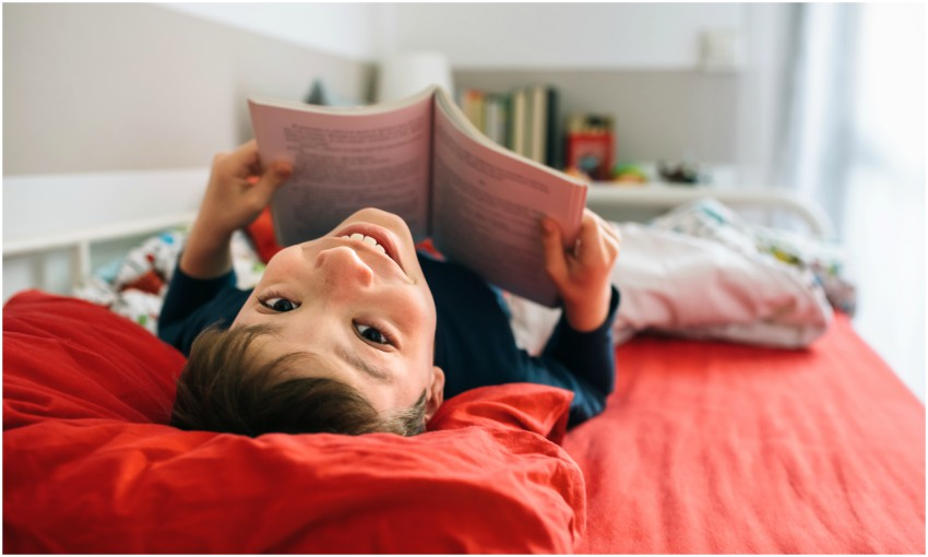 Boy lies on bed holding book and smiles upside-down at camera