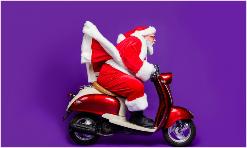 Santa riding a red scooter