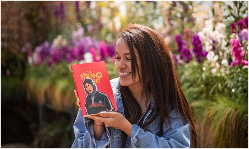Young woman in garden holding novel The Pōrangi Boy, smiling