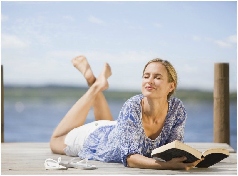 Woman lies tummy-down on a jetty, legs kicked up, propped on elbows with book.