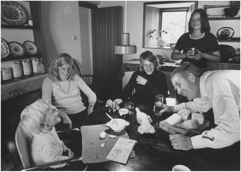 Black and white photograph of family laughing at kitchen table