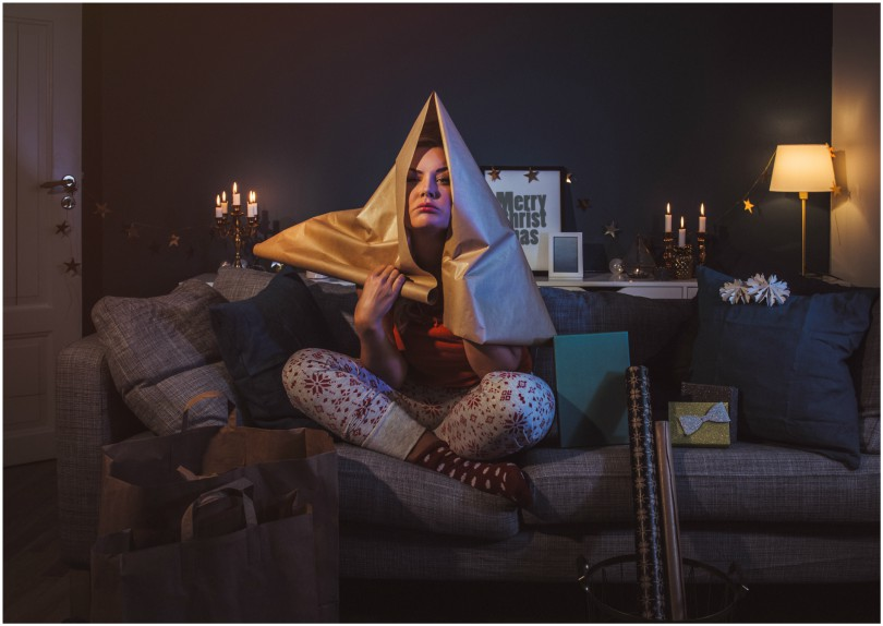 Woman on couch with wrapping paper over head, looking stressed