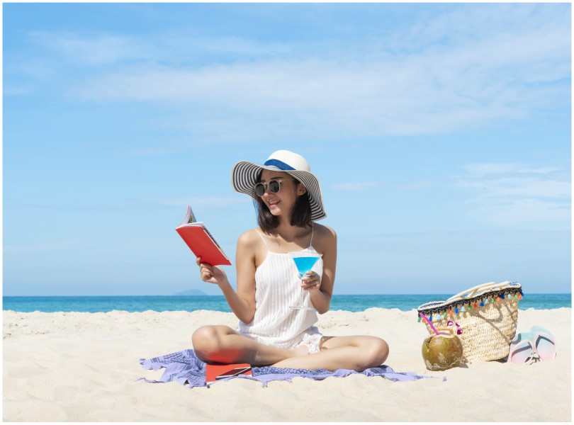 Woman sitting cross-legged on beach, holding book in one hand and drink in the other.