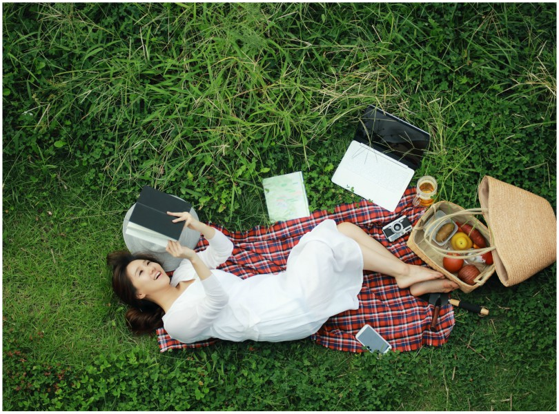 Woman lying on her back on picnic rug, curled up, holding book over her head.
