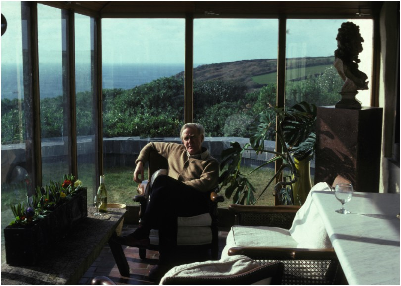 Man relaxes in conservatory with view over cliffs and sea.