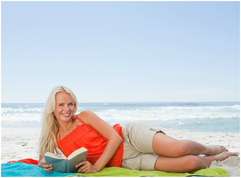 Woman lying on her side on the beach, smiling, reading.