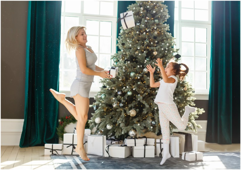 Woman and child dancing around Christmas tree, throwing packages.