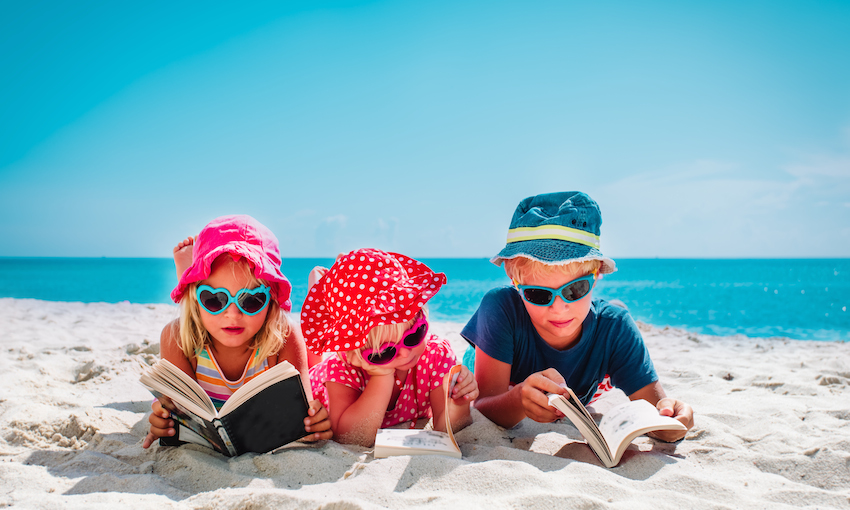 Three kids lying on tummies on beach, reading books
