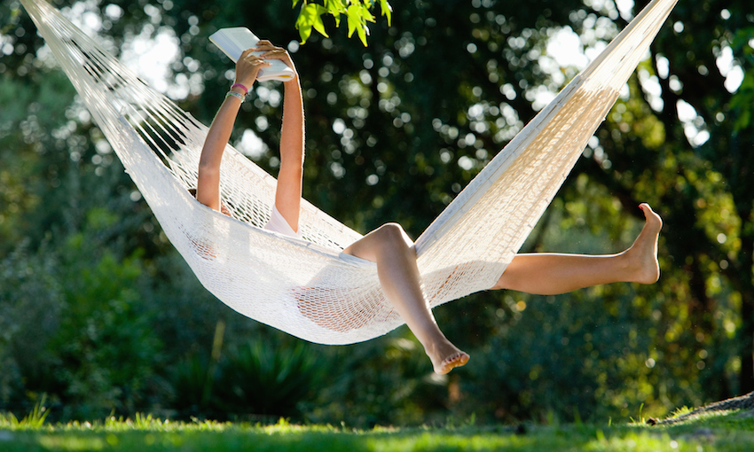 A person reading in a hammock, limbs akimbo