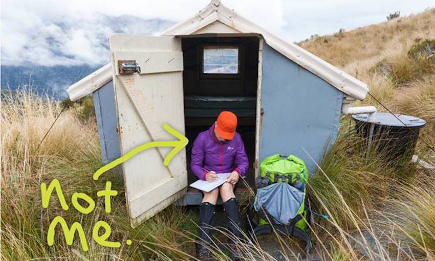 A hiker in front of a hut, with 'not me' written on it