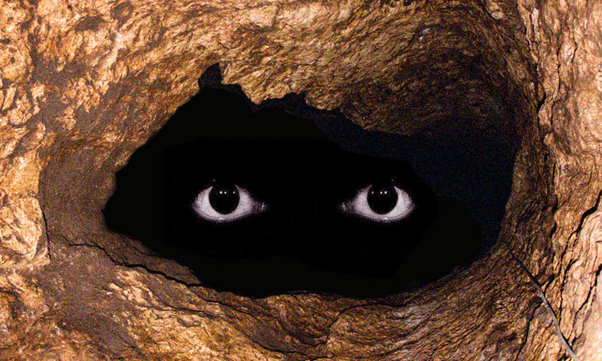 a deep, dark cave with a pair of scary eyes floating in it