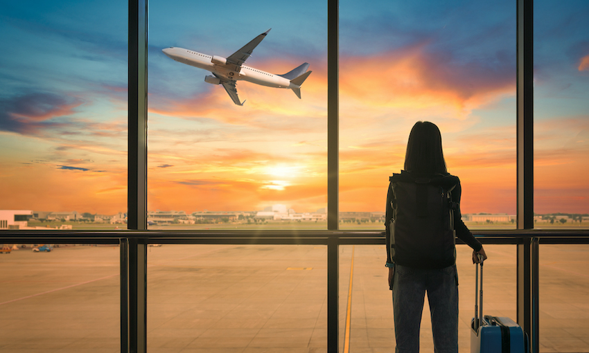 Silhouette of person standing watching passenger jet take off into sunset