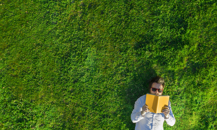 Aerial photo of young man lying in bright green grass, reading