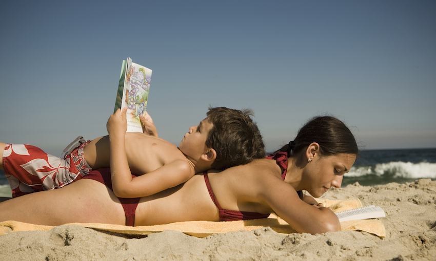 A woman lies on her front, reading, with a small boy lying on his back on top of her, reading. On a beach.