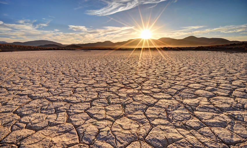 Photo of dry, cracked earth in the desert with a sunset over a mountain range in the background.
