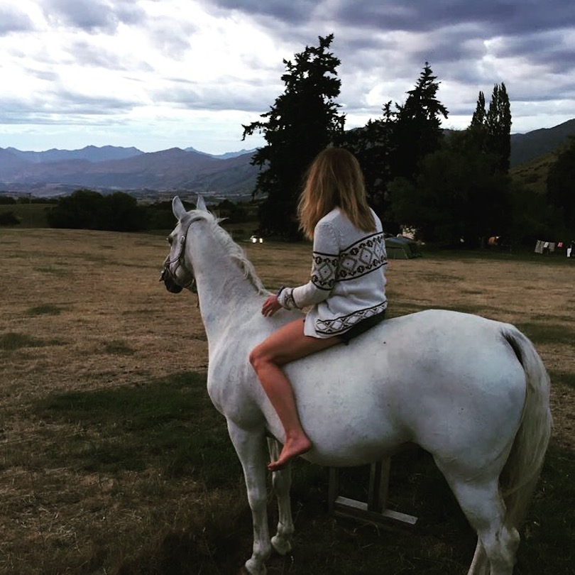 Woman on horse, facing away from camera, looking at mountain range in distance.