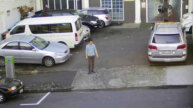 A lone man stands in a carpark, smoking, surrounded by cars.