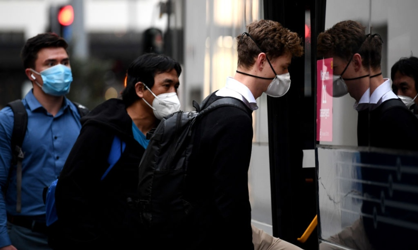 People getting on a bus in Auckland wearing masks (Getty Images)