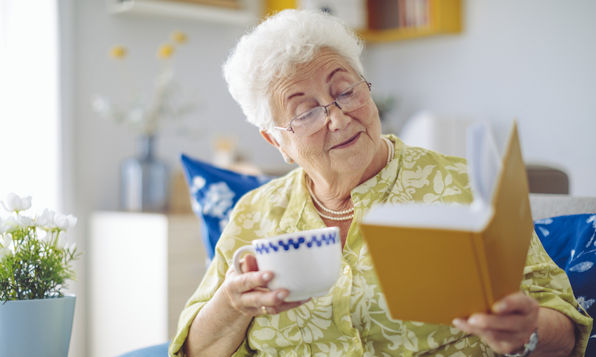 Senior woman holding a cup of tea and a book, looking delighted