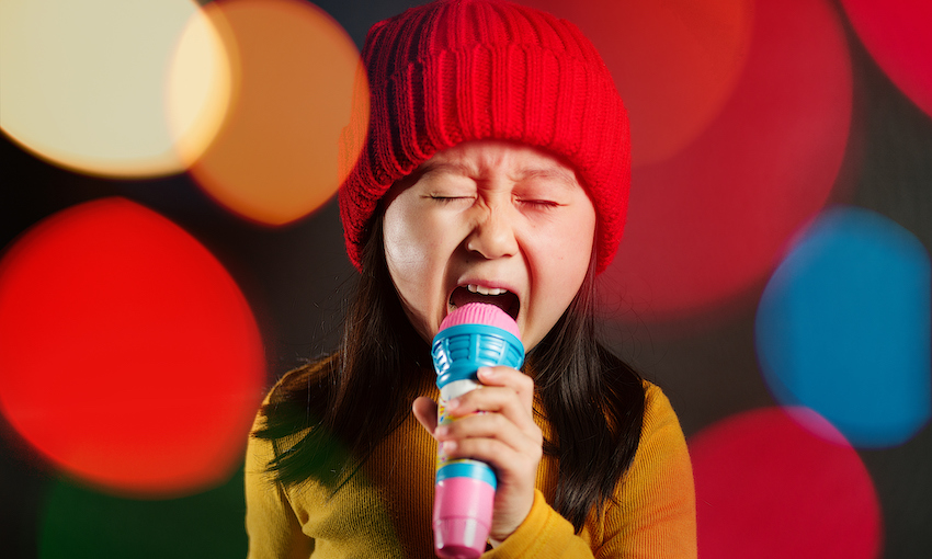 Young girl wearing red beanie, singing into karaoke mic, colourful lens flare in background
