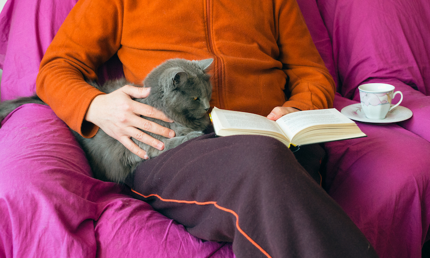 Woman in cardigan and trackpants reads book with cat in lap and cup of tea.