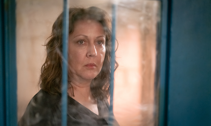 Rima Te Wiata as Susan Armstrong, gazing through the small window of a jail cell door.