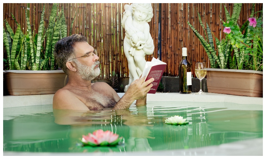 Mature man in bath with waterlilies and wine, reading a book