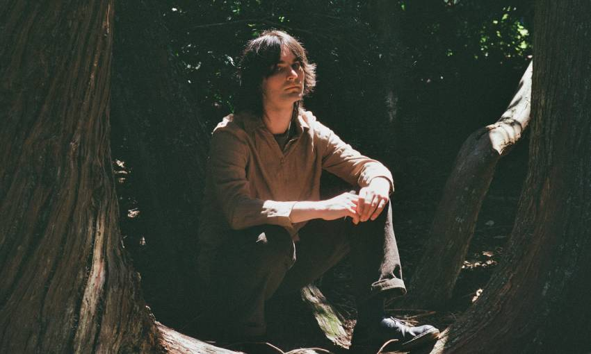 Kane Strang sits on a log in the woods, sunlight landing on his face and hands