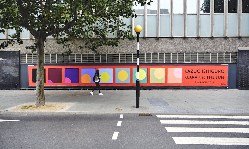 A photograph of a zebra crossing and a very long billboard for Kazuo Ishiguro's novel Klara and the Sun