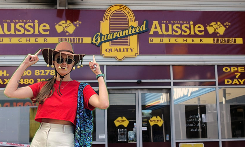 Author, wearing cork hat, points up at Aussie Butcher sign.