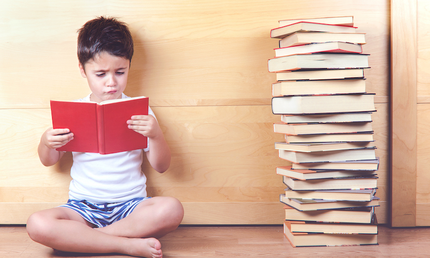 Cross-legged boy reads a book with a stack of books beside him.