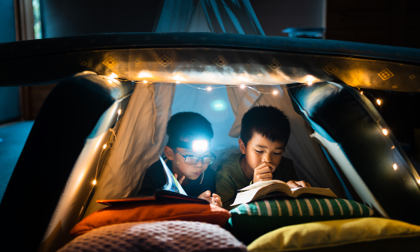 A cushion fort set up in a dark room, with fairy lights, two little boys reading books inside.
