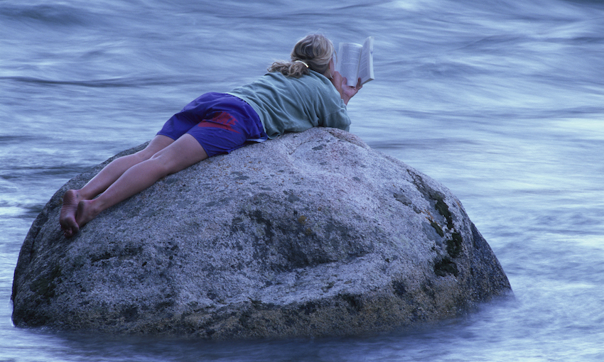 A woman lies on a rock in the middle of a river, reading