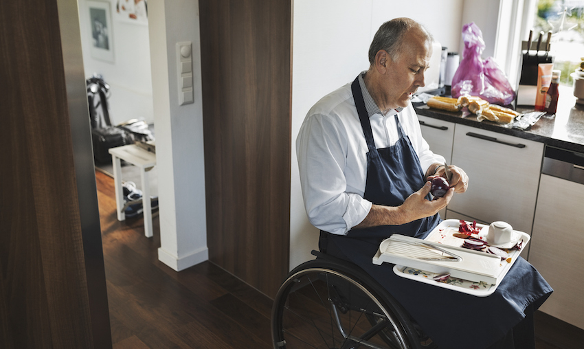 Disabled man in wheelchair cutting onion at kitchen