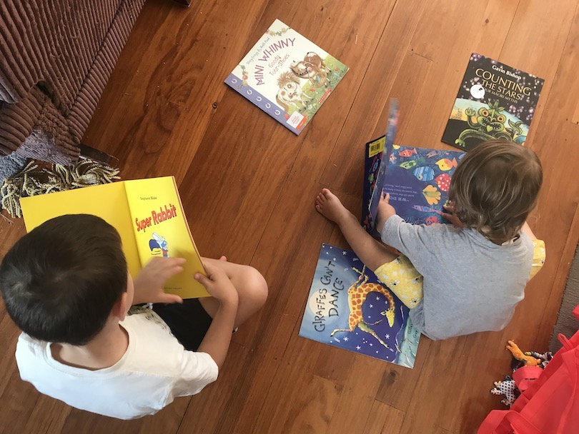 Two young children, photographed from above, surrounded by picture books