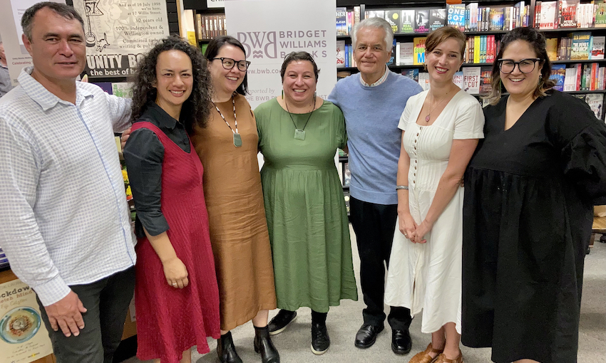 Seven people photographed together in a bookstore, happy