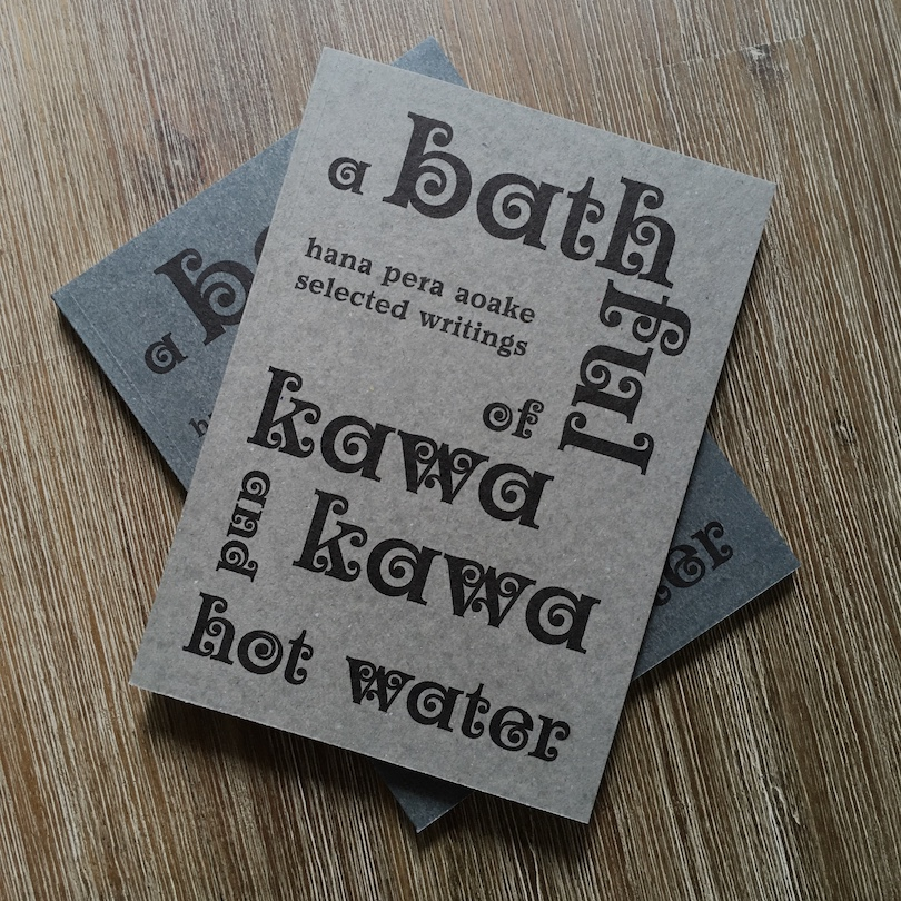 Two books, one grey and one a muted blue, both A Bathful of Kawakawa and Hot Water