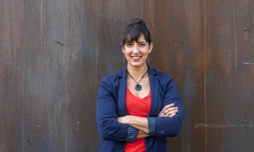 imche fourie wearing a blue blazer and red shirt, leaning against a wall with her arms crossed, smiling