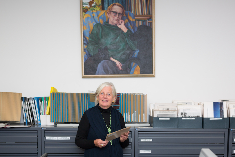 Senior woman stands in front of filing cabinets at a library, a huge painting hanging behind her.