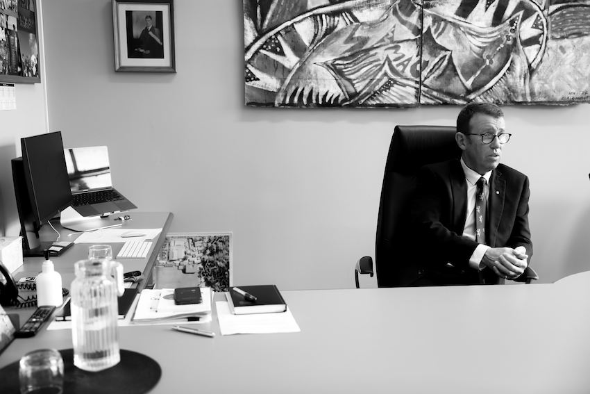 Patrick Drumm sits behind a large desk, eyes looking off camera, and talking to someone