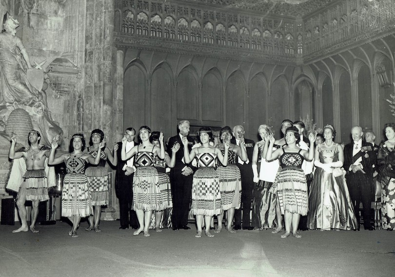 A black and white image of a pōwhiri, men and women in evening dress in background.