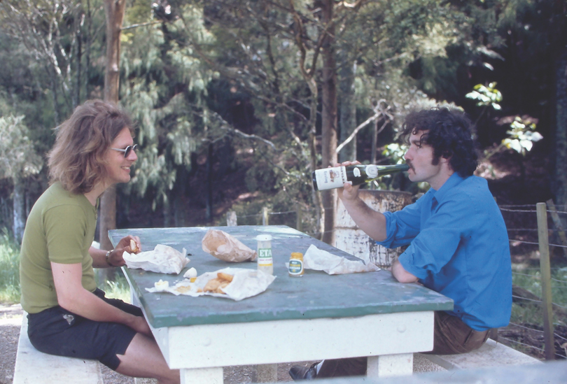 Two men at a picnic table, one swigging from a bottle, long hair and stubby shorts.