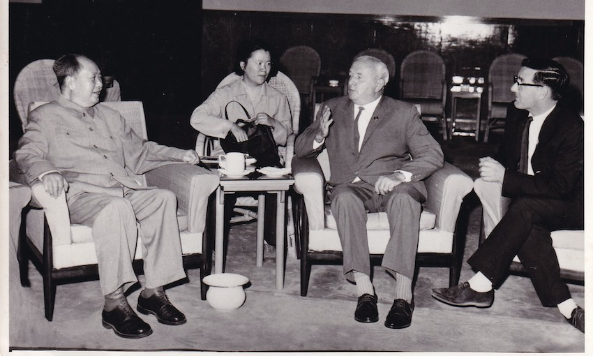 An old black and white photograph showing four people in a formal meeting,